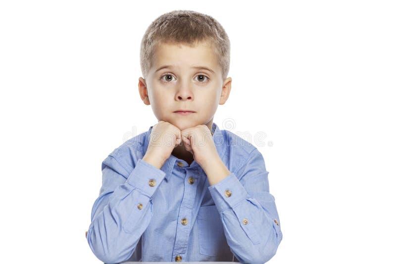 Menino bonito da idade escolar com uma cara surpreendida que senta-se na tabela Isolado no fundo branco imagens de stock