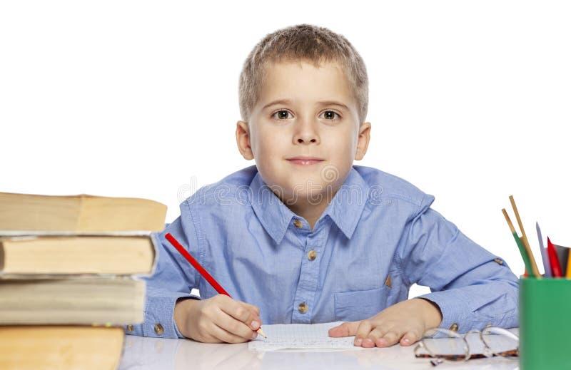 Menino bonito da idade escolar que faz trabalhos de casa na tabela É interessante aprender Isolado em um fundo branco fotos de stock