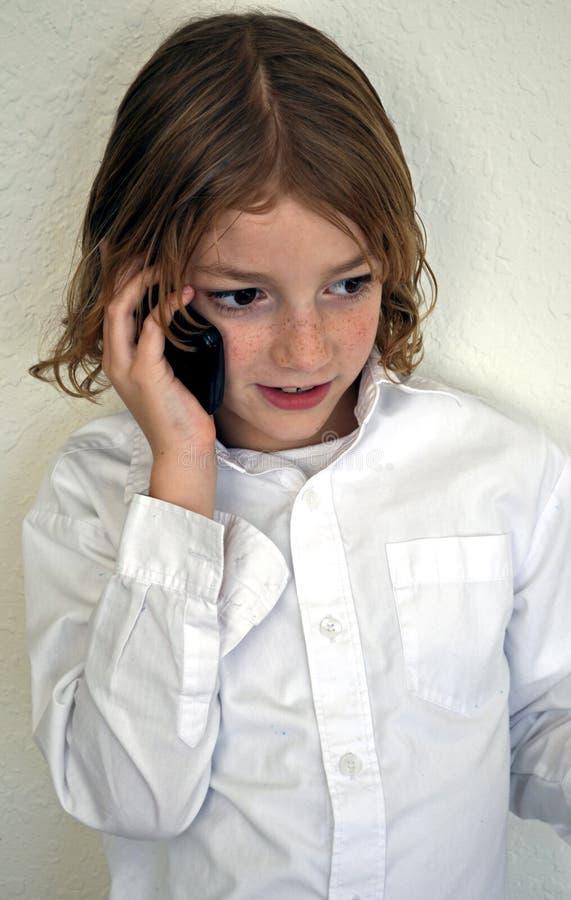 Menino bonito da juventude que fala no telefone fotos de stock royalty free