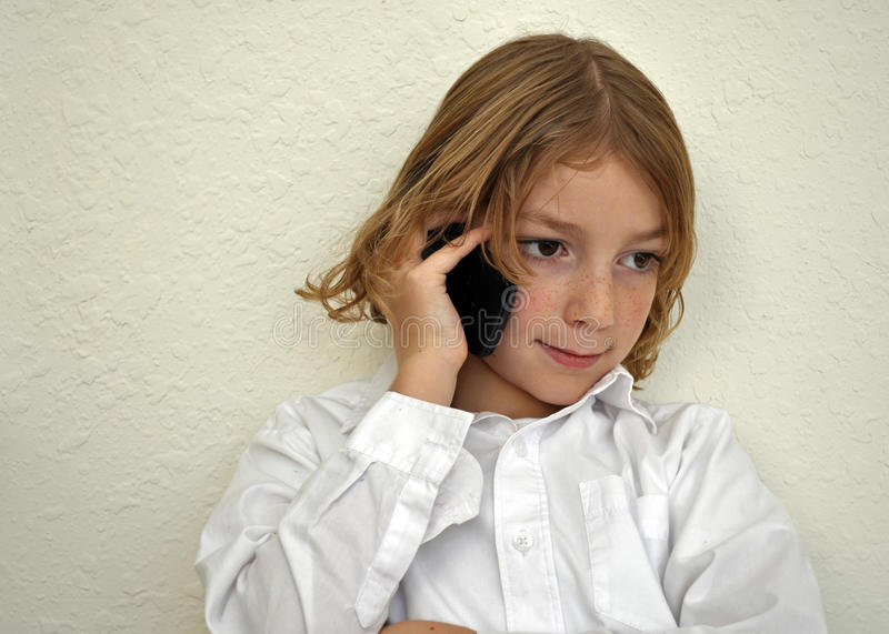 Menino bonito da juventude que fala no telefone imagens de stock