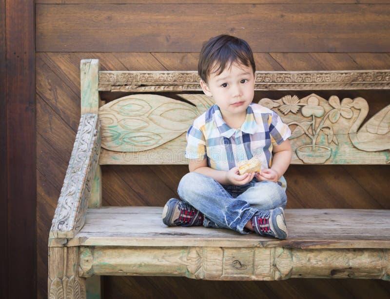 Menino bonito da raça misturada que senta-se no banco que come o sanduíche imagens de stock