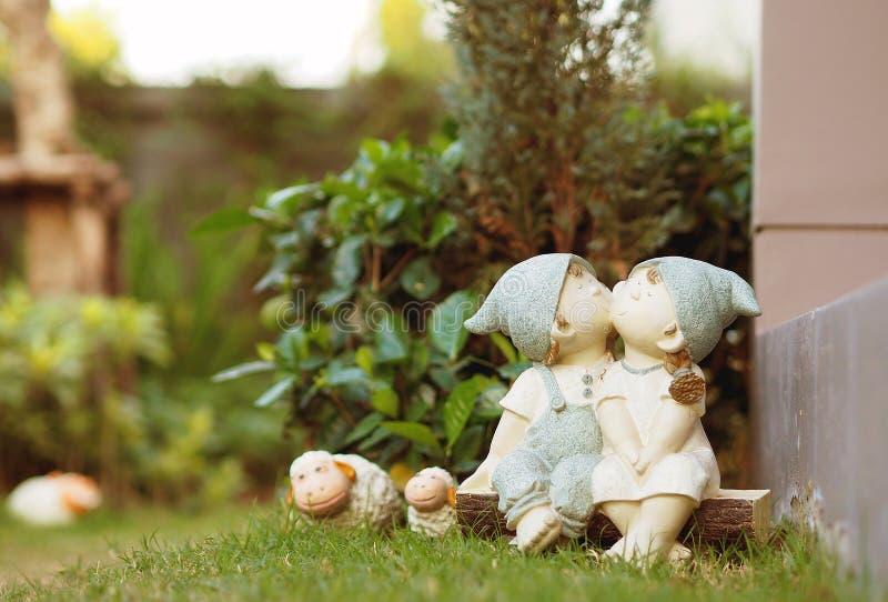Menino bonito das bonecas dos pares que beija a menina imagem de stock royalty free
