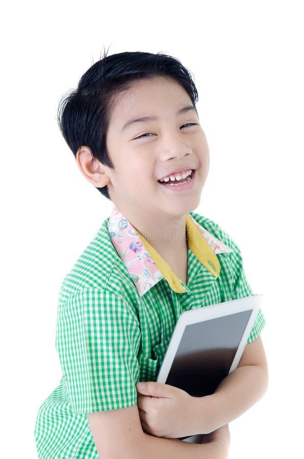 Menino bonito de Tailândia do asiático com o computador da tabuleta no backgro isolado imagens de stock