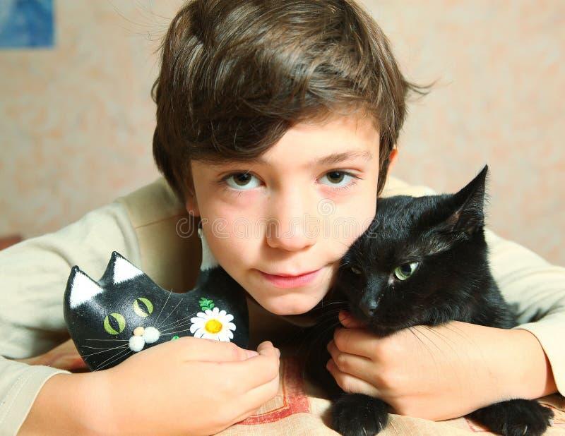 Menino bonito do preteen com o gato preto na tabela imagens de stock royalty free