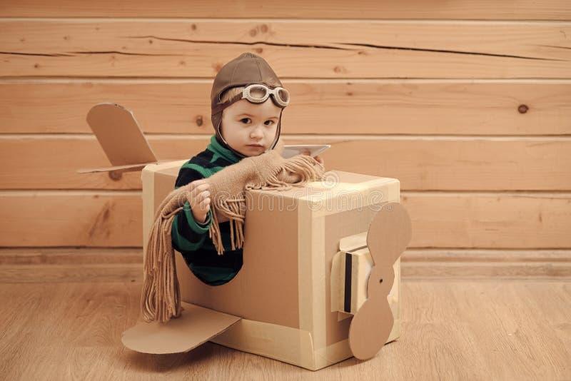 Menino bonito do sonhador que joga com um avião do cartão fotografia de stock royalty free