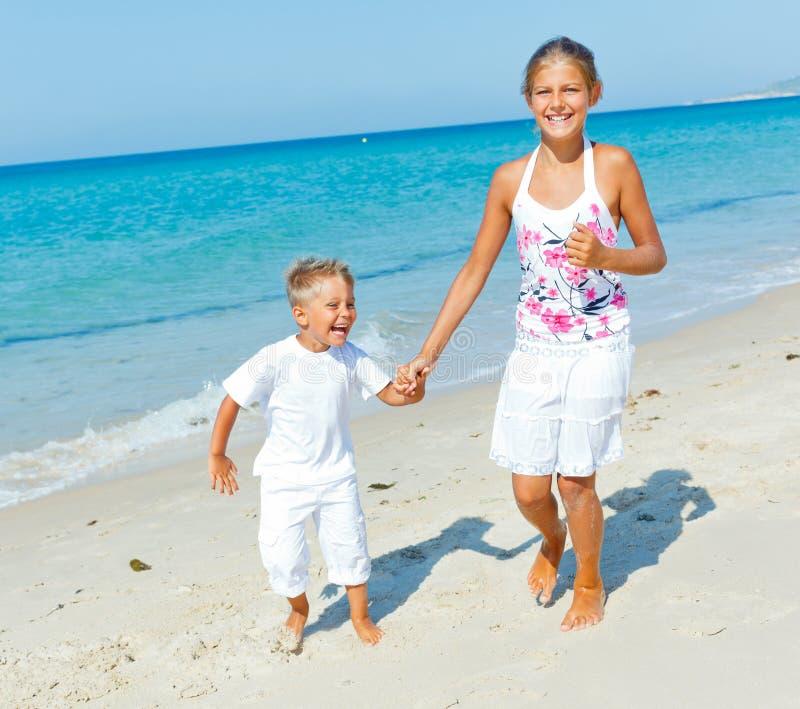 Menino bonito e menina na praia imagens de stock royalty free
