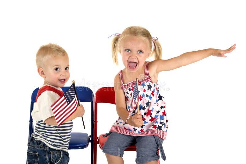 Menino bonito e menina que guardam a expressão bonito das bandeiras americanas foto de stock royalty free