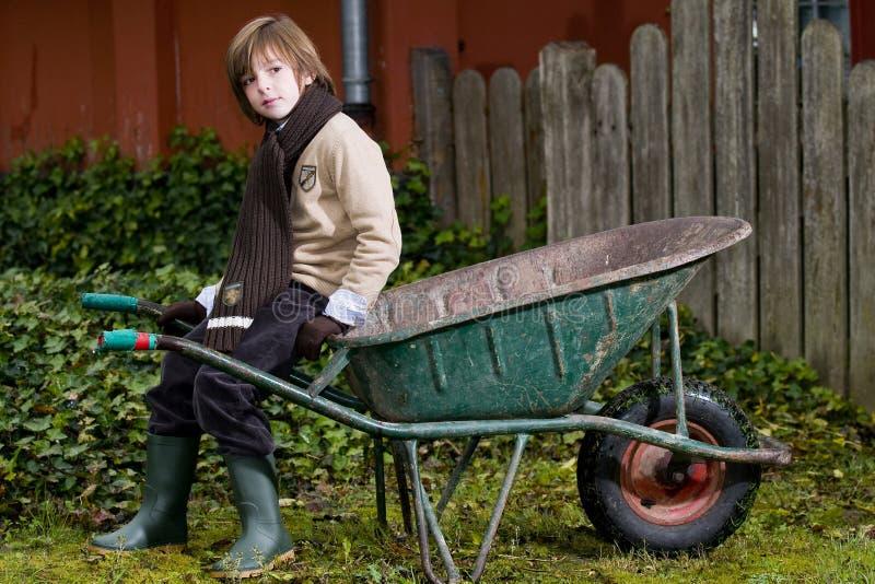 Menino bonito e wheelbarrow foto de stock royalty free
