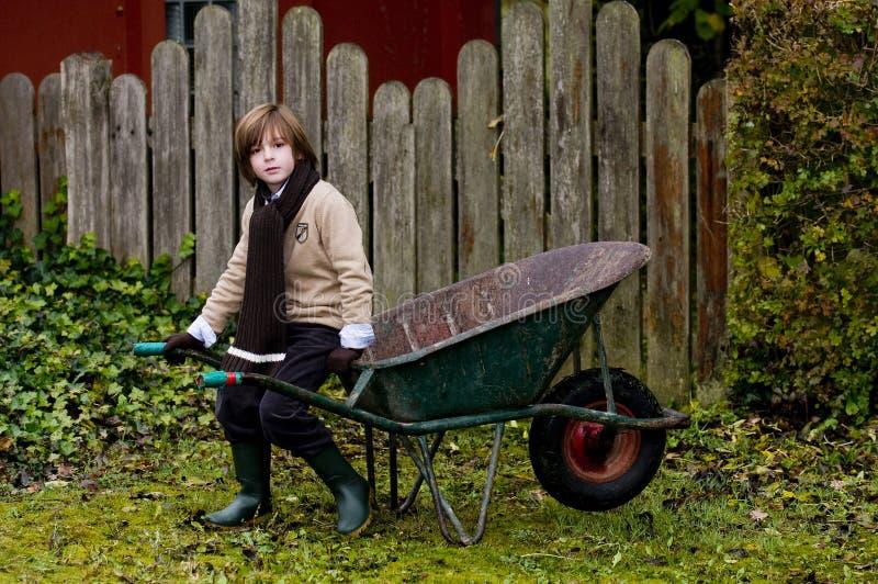 Menino bonito e wheelbarrow imagem de stock royalty free