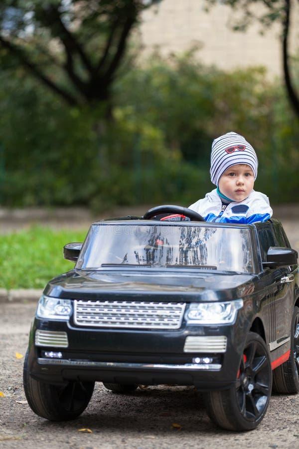 Menino bonito em montar um carro bonde preto no parque imagens de stock