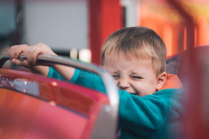 Menino bonito em um carro do carrossel fotografia de stock royalty free