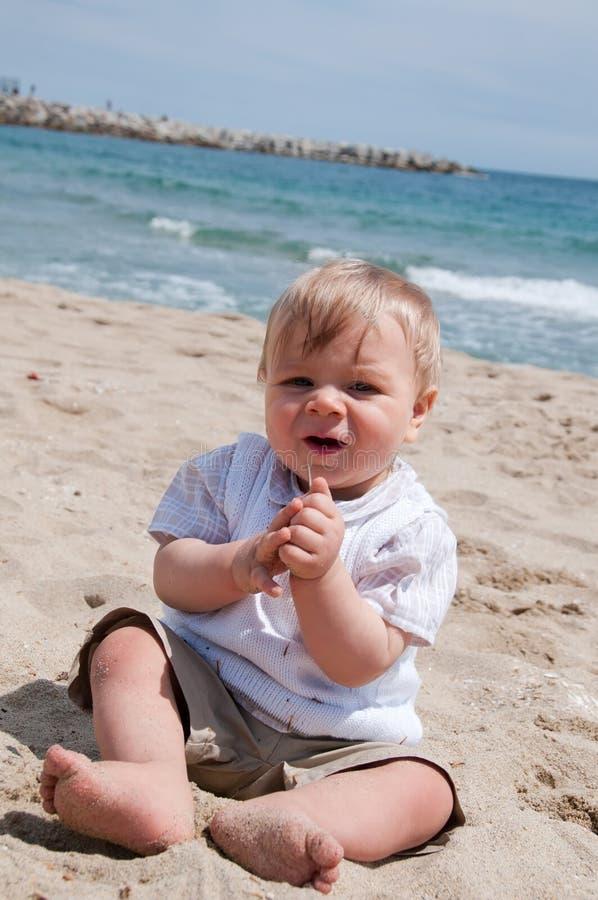 Menino bonito feliz que senta-se na praia imagens de stock royalty free