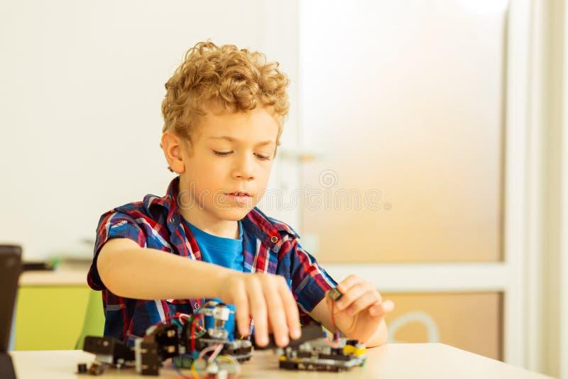 Menino bonito inteligente que está sendo interessado na ciência da robótica fotografia de stock