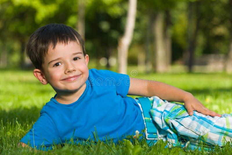 Menino bonito na camisa azul na grama. foto de stock