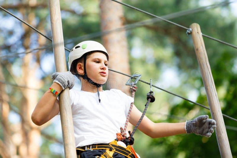 Menino bonito na camisa branca de t no parque da atividade da aventura com capacete e equipamento de segurança imagens de stock