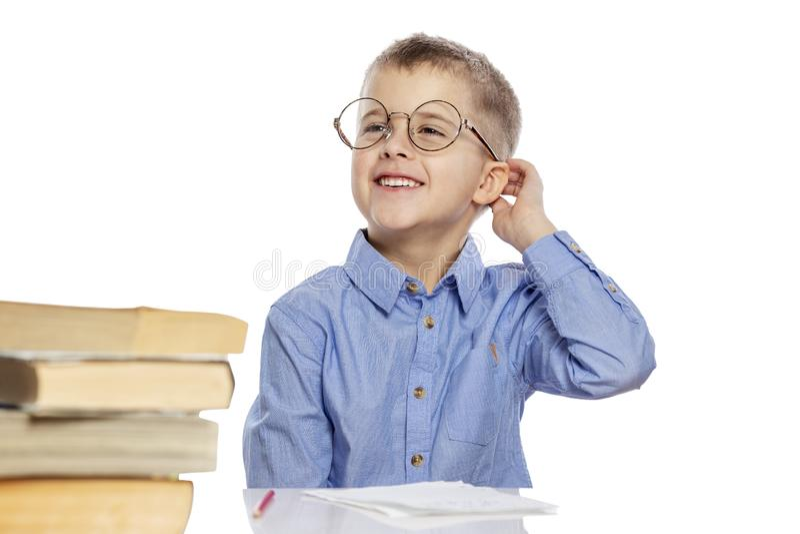 Menino bonito nos vidros da idade escolar que fazem trabalhos de casa na tabela e no riso É interessante aprender imagens de stock royalty free