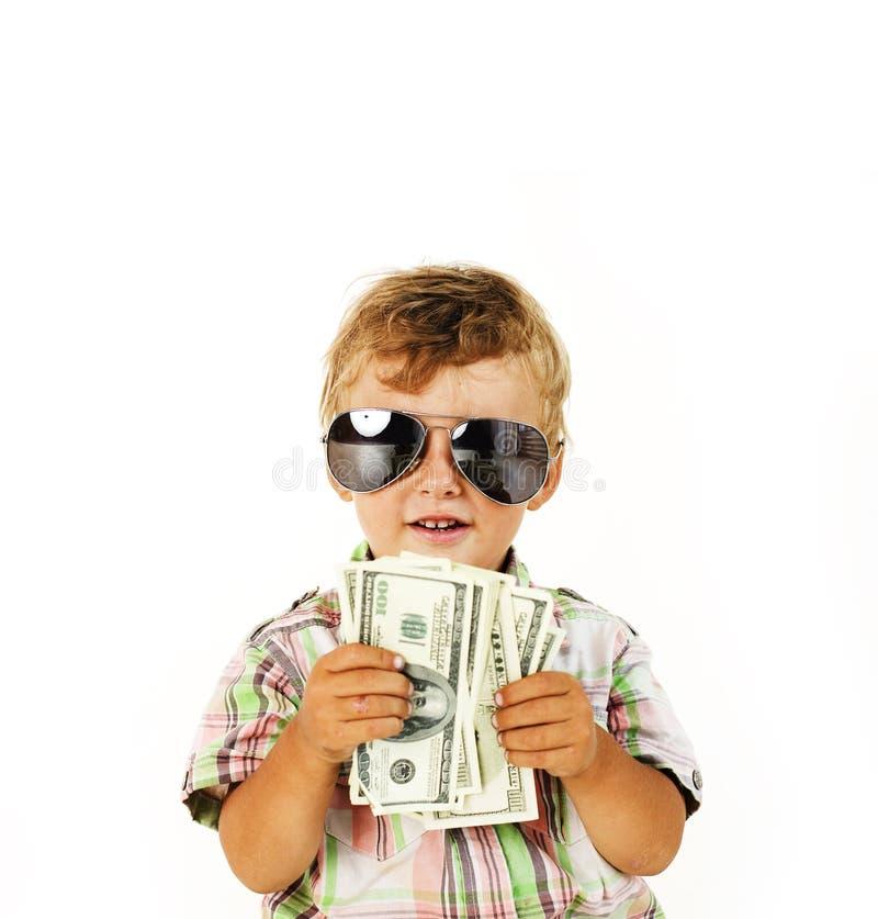Menino bonito novo que guarda o lote do dinheiro, dólares americanos isolados perto acima fotos de stock