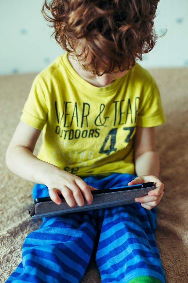 Menino bonito pequeno em um t-shirt verde que joga jogos em uma tabuleta e que olha desenhos animados Conceito do apego imagem de stock royalty free