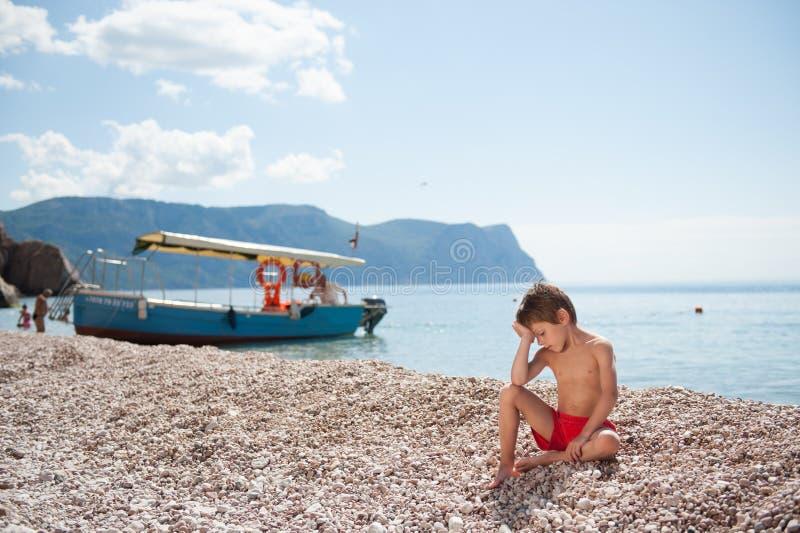 Menino bonito pequeno pensativo no short vermelho que senta-se na praia do verão com o barco no mar fotografia de stock