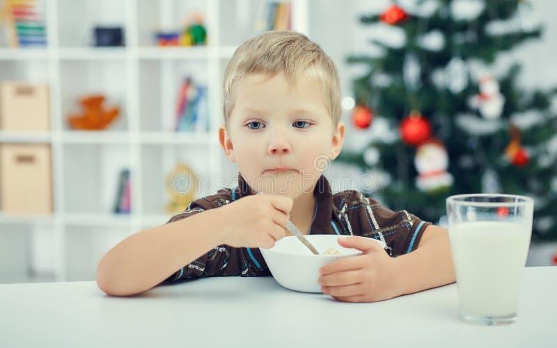 Menino bonito pequeno que come o café da manhã na véspera do ano novo Árvore de Natal no fundo imagens de stock royalty free