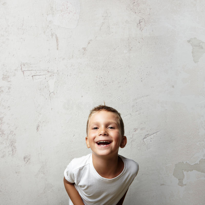 Menino bonito pequeno que ri da câmera Cocrete foto de stock royalty free
