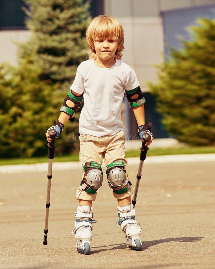 Menino bonito que aprende rollerblading foto de stock royalty free
