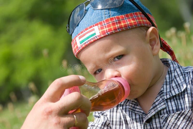 Menino bonito que bebe do frasco plástico fotografia de stock