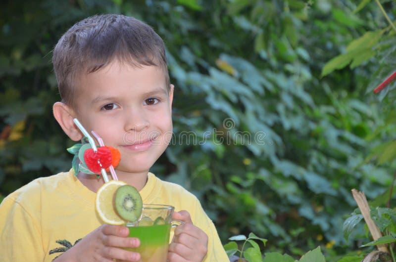 Menino bonito que bebe o batido saudável do suco de frutos do cocktail no verão Criança feliz que aprecia a bebida orgânica imagens de stock