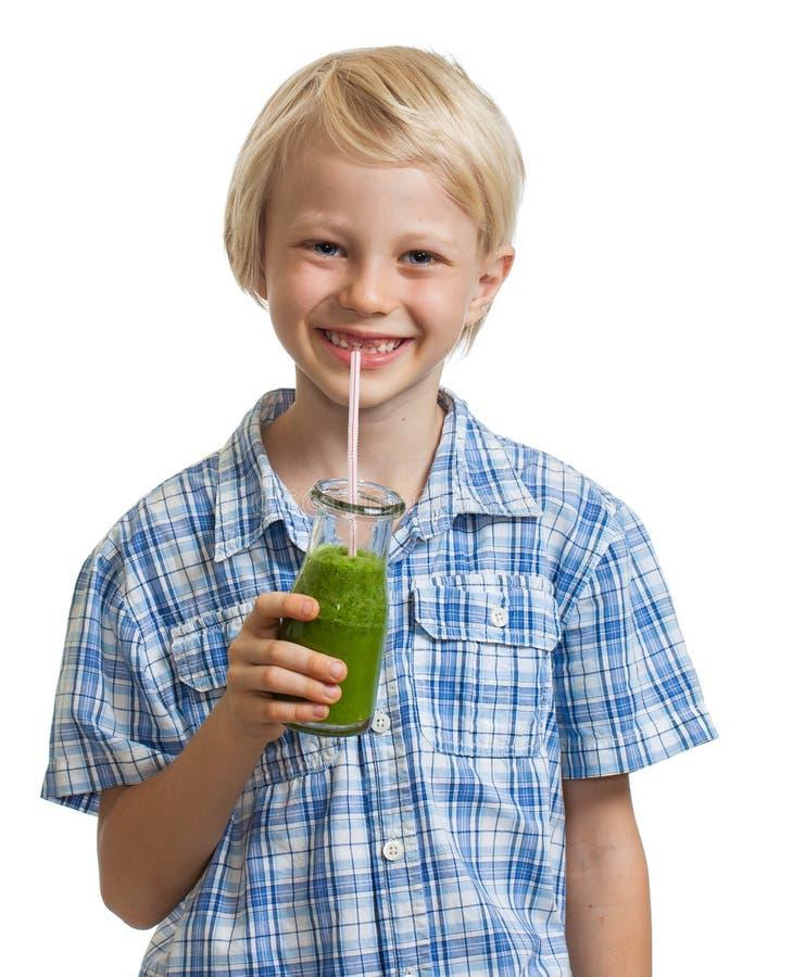 Menino bonito que bebe o batido verde fotografia de stock royalty free