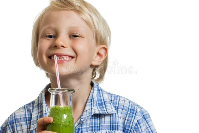 Menino bonito que bebe o sorriso verde do batido imagem de stock royalty free