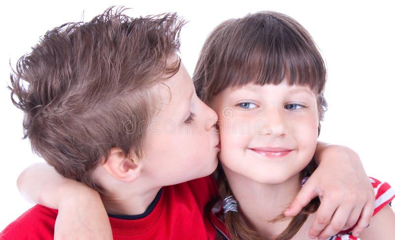 Menino bonito que beija uma menina agradável imagem de stock