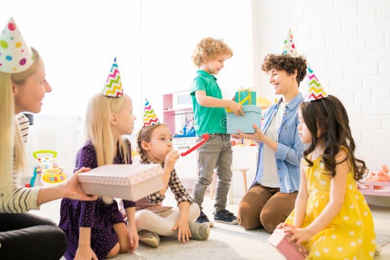 Menino bonito que dá caixas de presente para serir de mãe na festa de anos fotos de stock royalty free