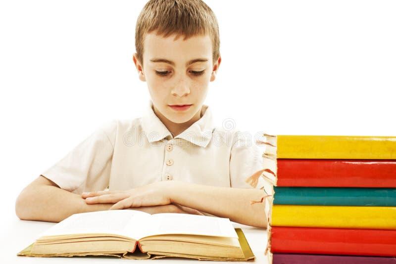 Menino bonito que estuda e que lê um livro em sua mesa fotografia de stock