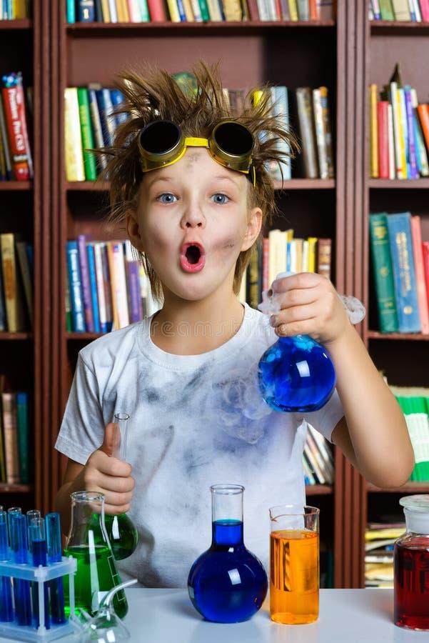Menino bonito que faz a pesquisa da bioquímica na química fotografia de stock