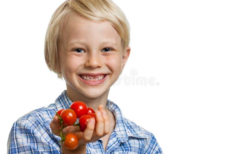Menino bonito que guarda o grupo dos tomates imagens de stock