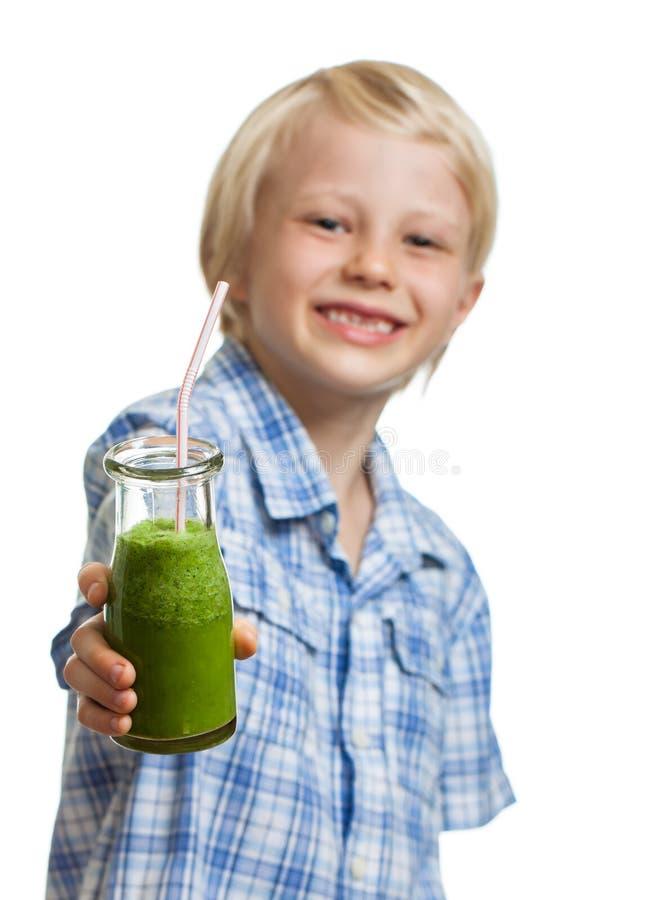 Menino bonito que guardara o batido ou o suco verde imagem de stock