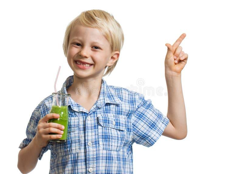 Menino bonito que guardara o batido verde e apontar imagem de stock royalty free
