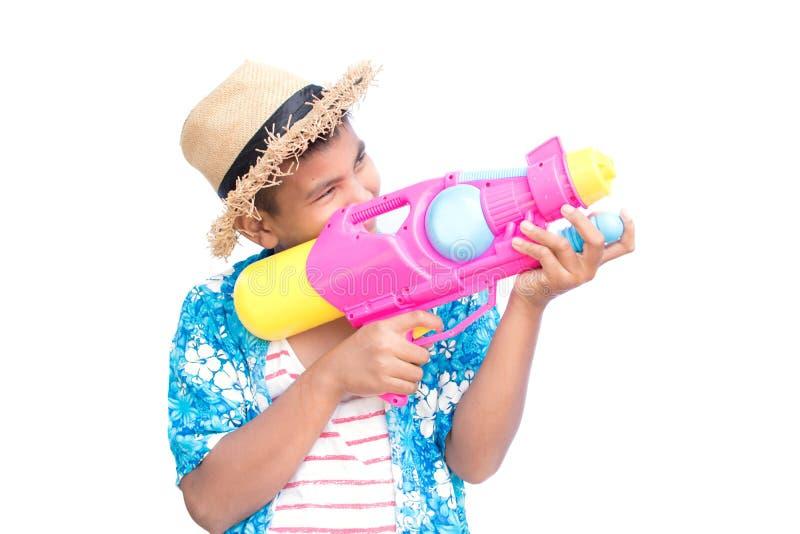 Menino bonito que joga a arma de água no fundo branco imagem de stock royalty free