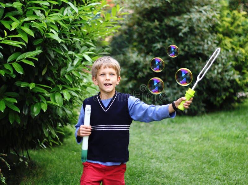 Menino bonito que joga com bolhas de sabão imagem de stock