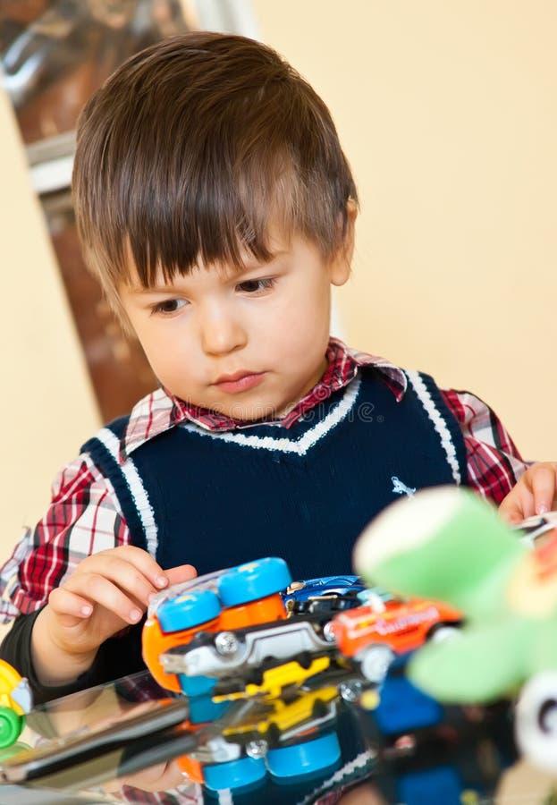 Menino bonito que joga com brinquedos foto de stock