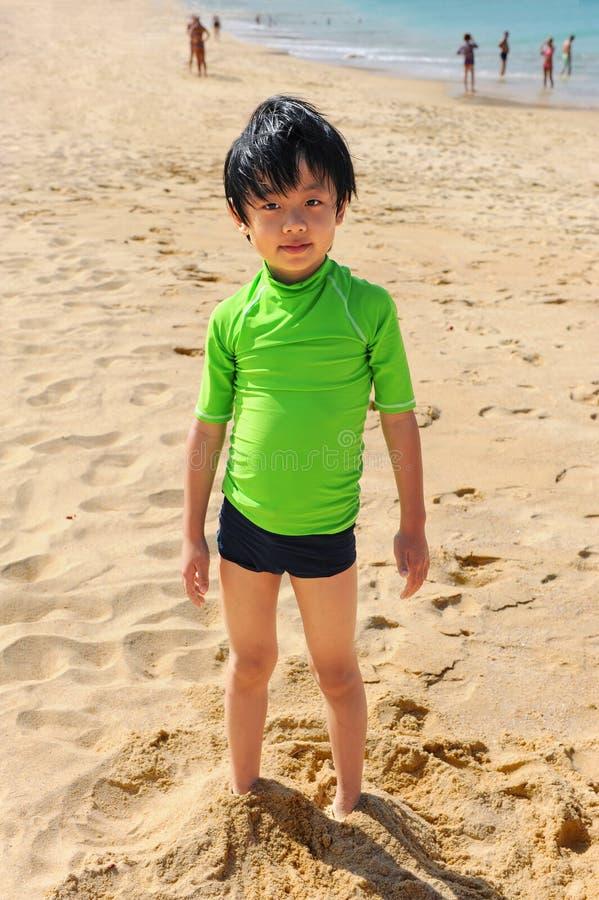 Menino bonito que joga na praia fotografia de stock royalty free