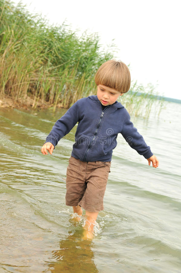 Menino bonito que joga na praia fotos de stock