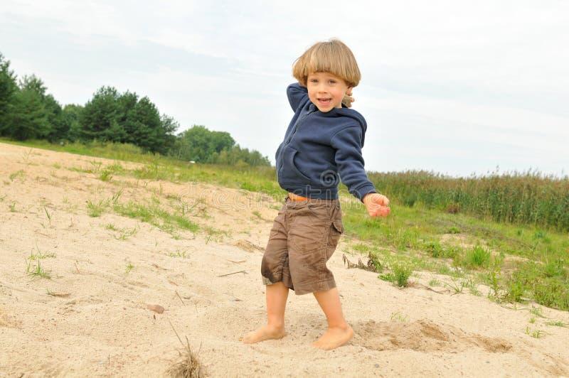 Menino bonito que joga na praia fotografia de stock