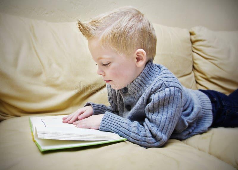 Menino bonito que lê um livro no sofá imagens de stock royalty free