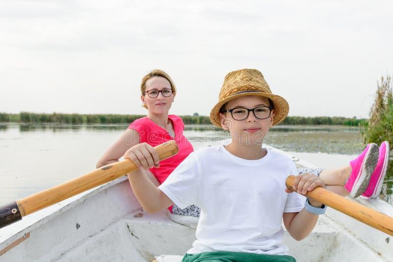 Menino bonito que rema com a mãe no barco Menino feliz ativo que tem f fotografia de stock royalty free