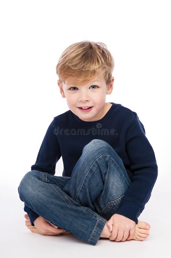 Menino bonito que senta equipado com pernas transversal. imagem de stock