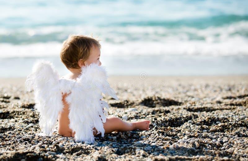 Menino bonito que senta-se na praia imagem de stock royalty free