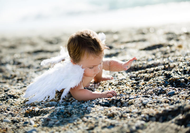 Menino bonito que senta-se na praia imagem de stock