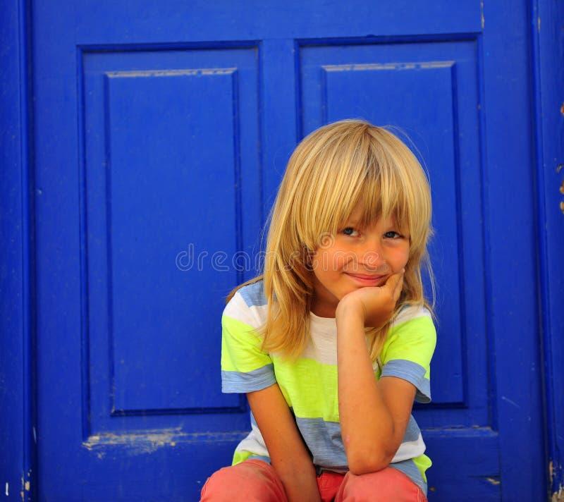 Menino bonito que senta-se no assoalho com a parte traseira de madeira azul profunda da porta sobre fotos de stock