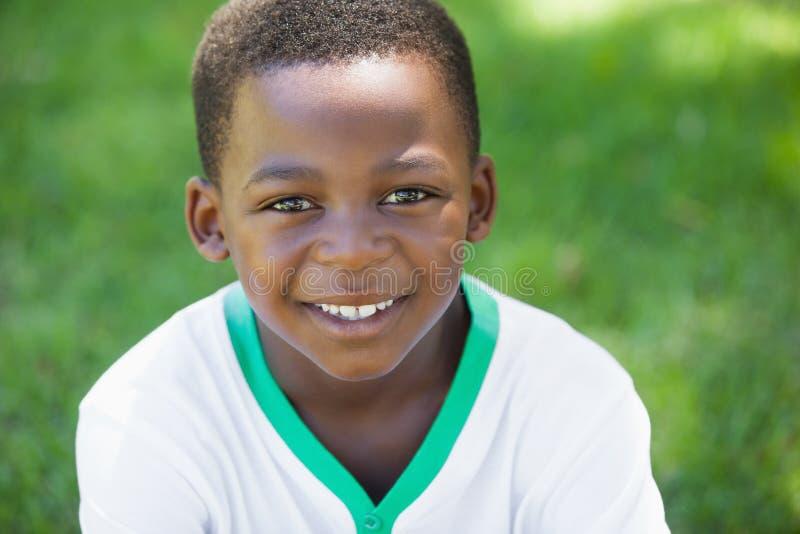 Menino bonito que sorri na câmera no parque imagens de stock